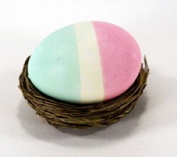 Tri-colored striped Easter egg in a nest.